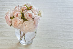 Wild pink roses in vase on white tablecloth Royalty Free Stock Photo