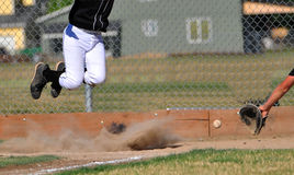 Wild pitch. Batter jumps to avpod the ball of a wild pitch hits the ground Stock Image