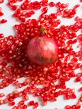 Wild pomegranate lies on the scattered grains of pomegranate on. A white background stock images