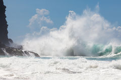 Wild, powerful wave splashing, crashing on rocky shore, under bl royalty free stock image