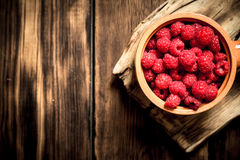 Wild raspberry in the Cup. On a wooden table Royalty Free Stock Photography