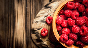 Wild raspberry in the Cup. On a wooden table Royalty Free Stock Images