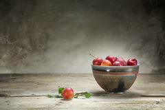 Wild red plums in a pottery bowl on an old wooden table Stock Photography