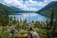 Lake in the mountains surrounded by old trees and large boulders. Wild remote place in the mountains. Huge boulders and old trees allow to forget about Royalty Free Stock Photography