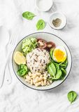 Wild rice, boiled egg, spinach, avocado puree, beans, tomatoes buddha bowl on light background, top view. Healthy vegetarian food Stock Photo