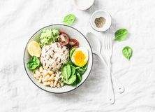 Wild rice, boiled egg, spinach, avocado puree, beans, tomatoes buddha bowl on light background, top view. Healthy vegetarian food Royalty Free Stock Photography