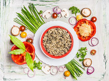 Wild rice dish and various vegetables and seasoning ingredients for tasty vegetarian cooking on light  rustic wooden background, t Royalty Free Stock Photos