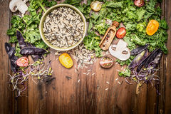 Wild rice with kale and vegetables ingredients for tasty cooking on rustic wooden background. Top view.  Vegetarian and healthy food concept Stock Photography