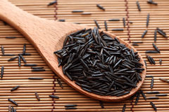 Wild rice in a wooden spoon. On bamboo napkin. Close-up Stock Photo