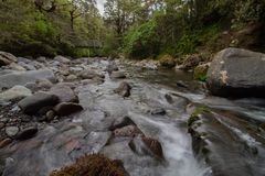 WIld river flows under a bridge in Tongariro Forrest Park New-Zealand. At tongariro hiking track stock photography