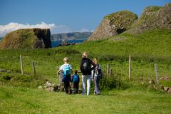 Hiking family, mother and three children walks on green, grass covered field, North Ireland Royalty Free Stock Image