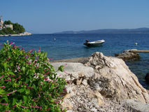Wild rocky beach in Croatia with a small boat. Beautiful beach in Croatia full of rocks and pebbles Stock Photography