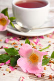 Wild rose flower and cup of tea on old rustic wooden background. Fresh blooming wild rose flowers and dried petals with tea grains, cup of hot tea on old wooden royalty free stock photography