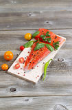 Wild Salmon and ingredients on wooden Plank for cooking. Vertical view of raw red salmon, skin side down, on maple wood grilling plank with seasoning and other Stock Photos