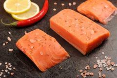 Wild salmon salted with himalayan pink salt, lemon and chili. Closeup Royalty Free Stock Photography