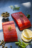 Wild salmon. Two pieces of raw wild salmon fish steaks with lemon, capers and herbs, ready to cook Stock Photography