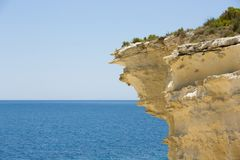 Malta, barbed rock formations over the blue sea. Wild sand stone cliff, blue sky and sea as background Royalty Free Stock Image