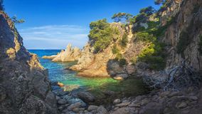 Wild seascape of bay in Mediterranean sea on clear sunny day. Amazing view of rocky shores against blue sky and coastline. Amazing sea nature of Costa Brava Stock Photo