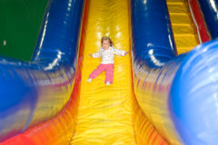 Wild slide. Adorable little blond girl comes down inflatable slide Royalty Free Stock Image