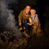 Mother and daughter travellers near campfire grilling sausages Royalty Free Stock Photo
