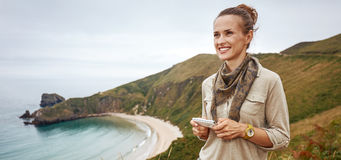 Happy woman hiker writing sms in front of ocean view landscape royalty free stock image