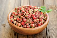 Wild strawberries Fragaria viridis with green leaf in wooden bow Stock Photo