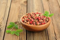 Wild strawberries Fragaria viridis with green leaves in wooden b Royalty Free Stock Images