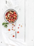 Wild strawberries in rustic metal bowl on white Stock Photos