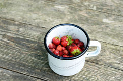 Wild strawberry in metal cup on wooden background Royalty Free Stock Image