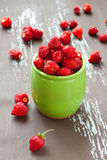 Wild Strawberry. Wild strawberries in a jar with some berries on background, selective focus Royalty Free Stock Photos