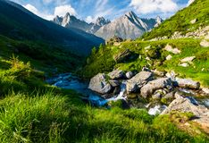 Wild stream among the rocks. Beautiful composite landscape with grassy hills in summer. mountain ridge with rocky peaks in the far distance under the blue sky Stock Photography