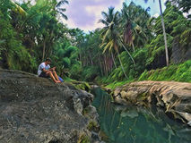 Wild tropical forest with calm river. Sitting man on riverside stone. Relax on tropic nature. Stock Photo