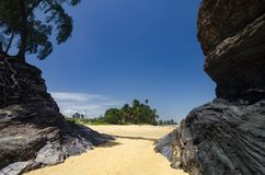 Wild tropical island and rocky sea shore under bright sunny day. And blue sky background stock photography