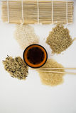 Wild types of rice. Different types of asian rice, chopsticks, straw matt for rolls, soy sauce Stock Photos
