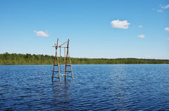 Wild vacation. Wooden swings are standing in the middle of the lake Royalty Free Stock Photos