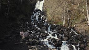 Wild waterfall in the mountains. Giant hill with a waterfalll. Clear water full of foam flowing between giant rocks. Beauties of the nature. Forest. Washing on stock video