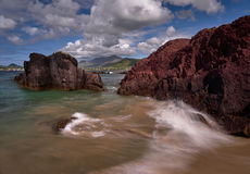 Wild waves at the coast of the Dingle peninsula. Waves hitting against a red rock on the Dingle peninsula, Ireland Stock Photography