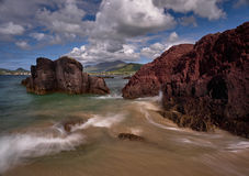 Wild waves at the coast of the Dingle peninsula. Waves hitting against a red rock on the Dingle peninsula, Ireland Stock Images