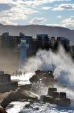 Wild waves splashing people near lighthouse Royalty Free Stock Photos