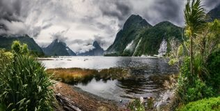 Wild Weather at Milford Sound Panorama. Wild weather conditions at Milford Sound with the clouds engulfing the mountain peaks - Panoramic view at Freshwater stock photos