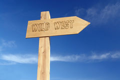 Wild West. Wooden signpost indicating Wild West direction over blue sky Royalty Free Stock Photos