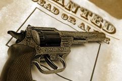 Wild west concept. Wild west revolver over wanted poster Stock Photo
