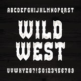 Wild West font. Vintage alphabet. Rough letters and numbers on a grunge wooden background. Stock Photo