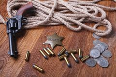 Wild west gun, ammunition and U.S. Marshal Badge. On wooden table action arms cowboy firearms power shot shotguns weapons western repeating lever-action war royalty free stock photo