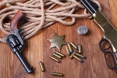 Wild west gun, ammunition and U.S. Marshal Badge. On wooden table action arms cowboy firearms power shot shotguns weapons western repeating lever-action war royalty free stock photography