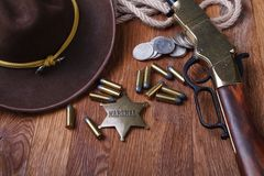 Wild west gun, ammunition and U.S. Marshal Badge. On wooden table action arms cowboy firearms power shot shotguns weapons western repeating lever-action war royalty free stock images