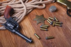 Wild west gun, ammunition and U.S. Marshal Badge. On wooden table action arms cowboy firearms power shot shotguns weapons western repeating lever-action war royalty free stock image