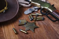 Wild west gun, ammunition and U.S. Marshal Badge. On wooden table action arms cowboy firearms power shot shotguns weapons western repeating lever-action war stock photo