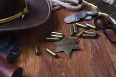 Wild west gun, ammunition and U.S. Marshal Badge. On wooden table action arms cowboy firearms power shot shotguns weapons western repeating lever-action war stock image