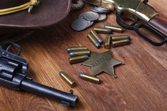 Wild west gun, ammunition and U.S. Marshal Badge. On wooden table action arms cowboy firearms power shot shotguns weapons western repeating lever-action war stock photography